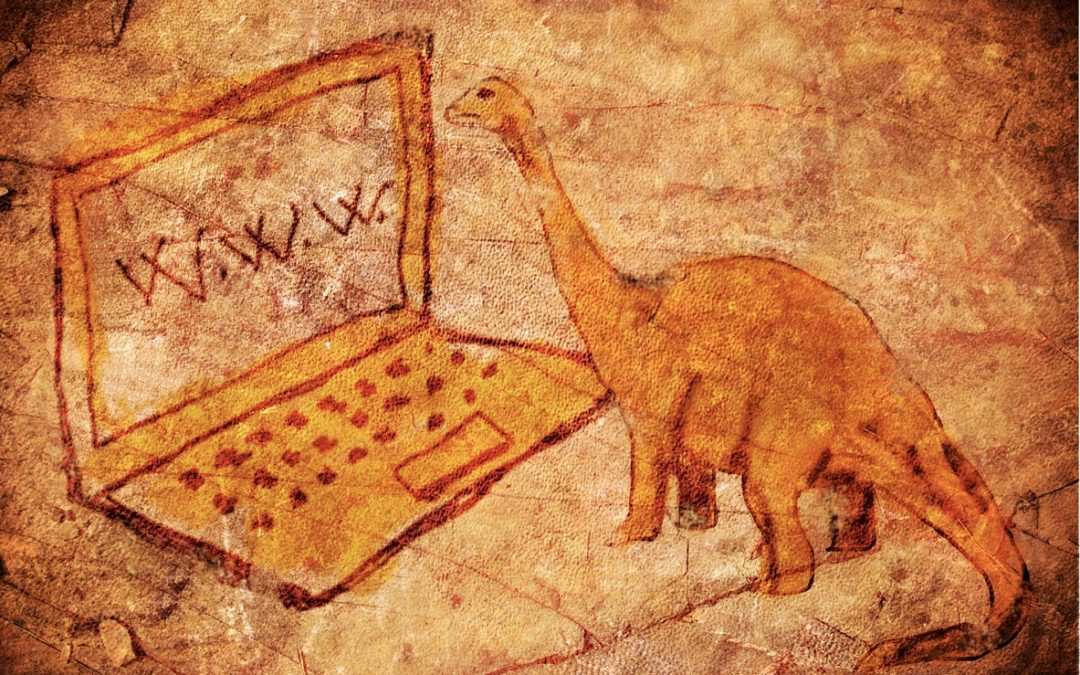 cave drawing of dinosaur staring at laptop screen
